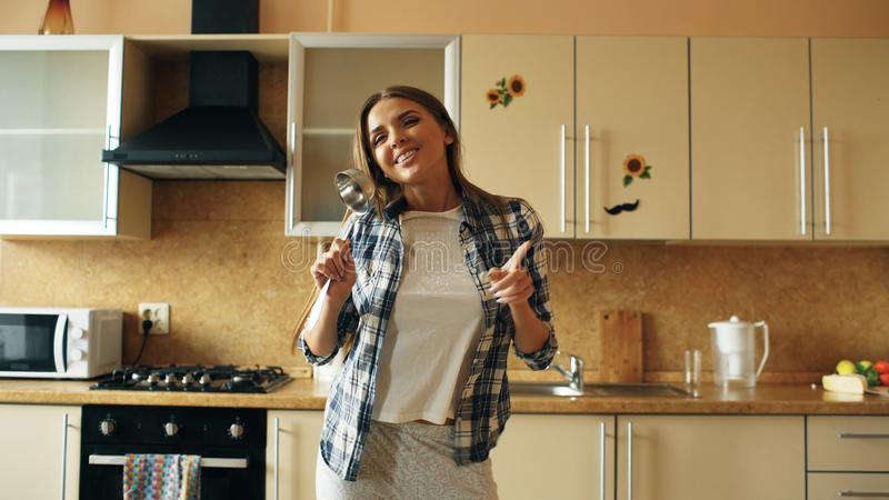 Cheerful young funny woman dancing and singing with ladle while having leisure time in the kitchen at home stock photos