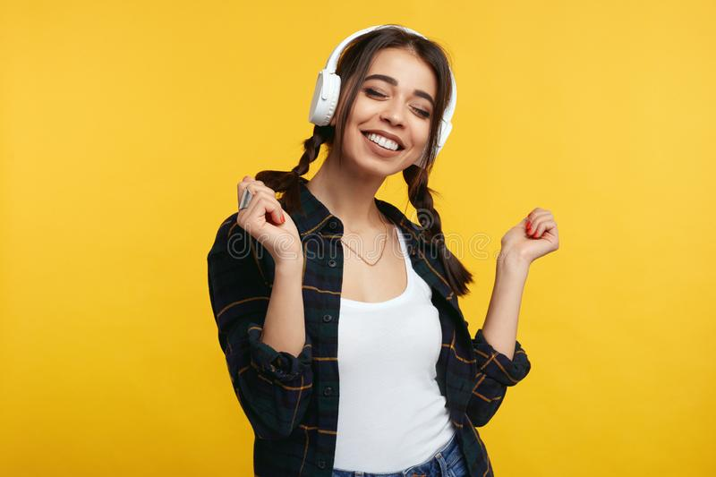 Cheerful young girl enjoy sound of music, closes eyes from pleasure while standing  over yellow background. Overjoyed young girl enjoy sound of music, closes stock images