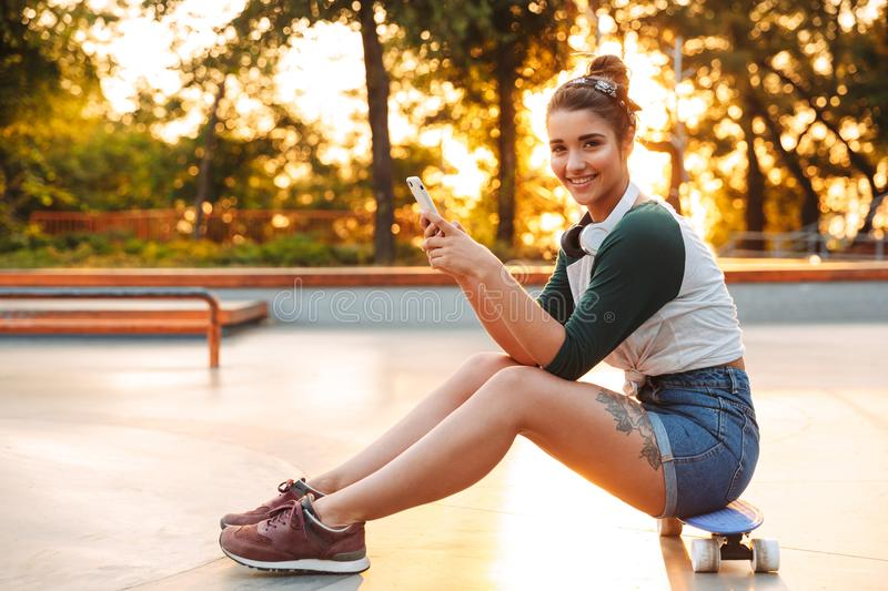 Cheerful young girl with headphones using mobile phone stock images