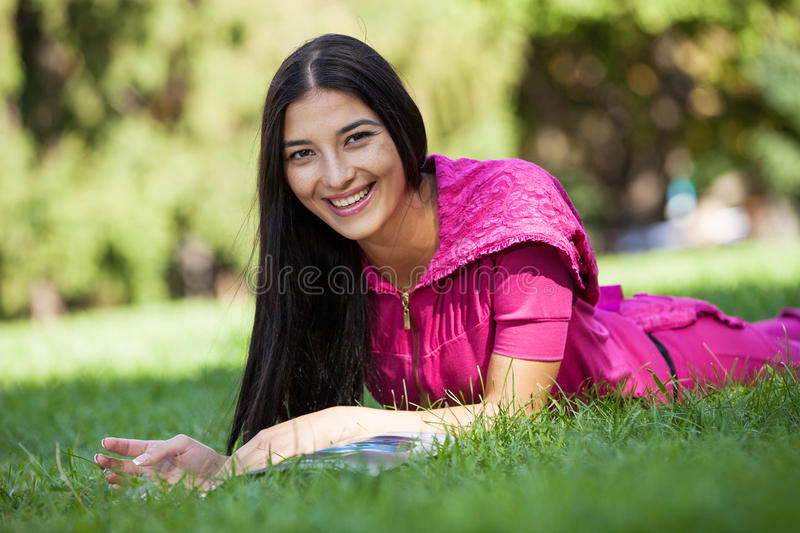 Cheerful young girl lying on grass in park royalty free stock image