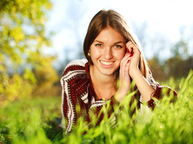 Cheerful young girl lying on green grass stock photography
