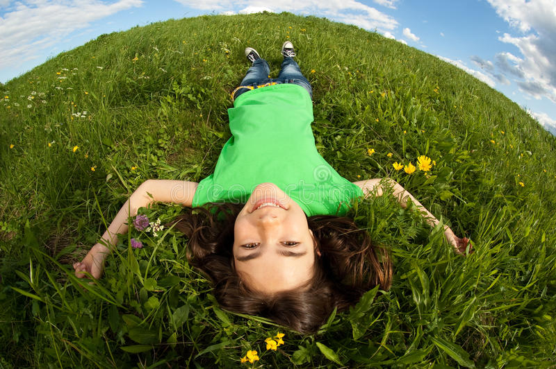 Cheerful young girl lying outdoor. Girl relaxing on green meadow royalty free stock photography