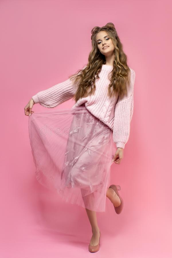 Pretty young girl in a pink sweater on a pink background with a haircut and curly long hair. stock images