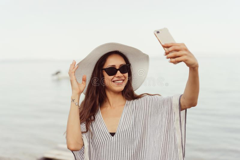 Cheerful young girl in summer hat and swimwear taking a selfie. Cheerful young girl in summer hat and swimwear spending time at the beach, taking a selfie with royalty free stock image