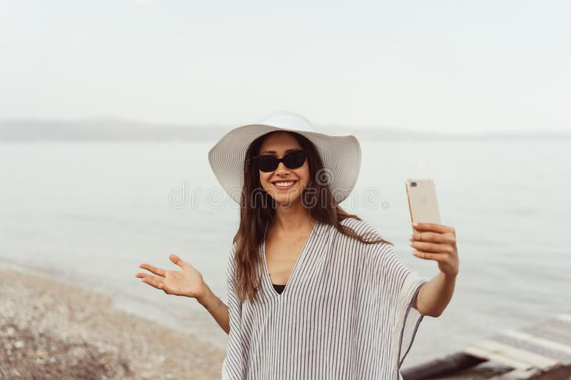 Cheerful young girl in summer hat and swimwear taking a selfie. Cheerful young girl in summer hat and swimwear spending time at the beach, taking a selfie with royalty free stock images