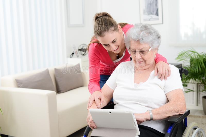 Cheerful young girl teaching internet with computer tablet and sharing time with an old senior woman on wheelchair. Cheerful young girl teaching internet with a royalty free stock images