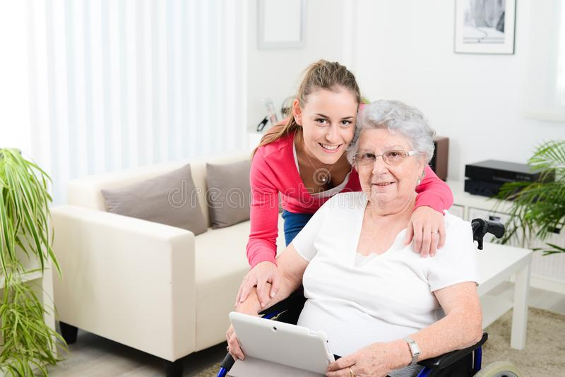Cheerful young girl teaching internet with computer tablet and sharing time with an old senior woman on wheelchair. Cheerful young girl teaching internet with a stock image