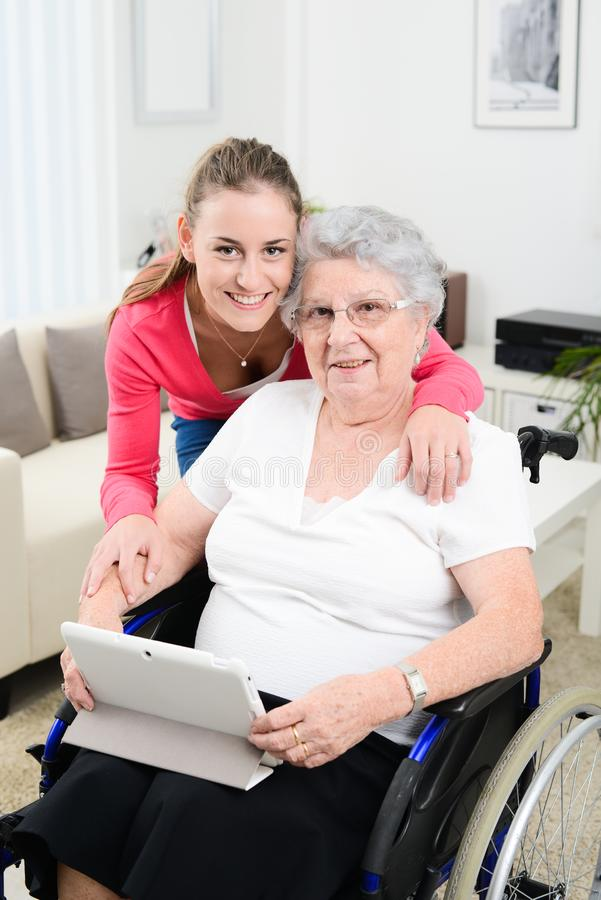 Cheerful young girl teaching internet with computer tablet and sharing time with an old senior woman on wheelchair. Cheerful young girl teaching internet with a stock photo