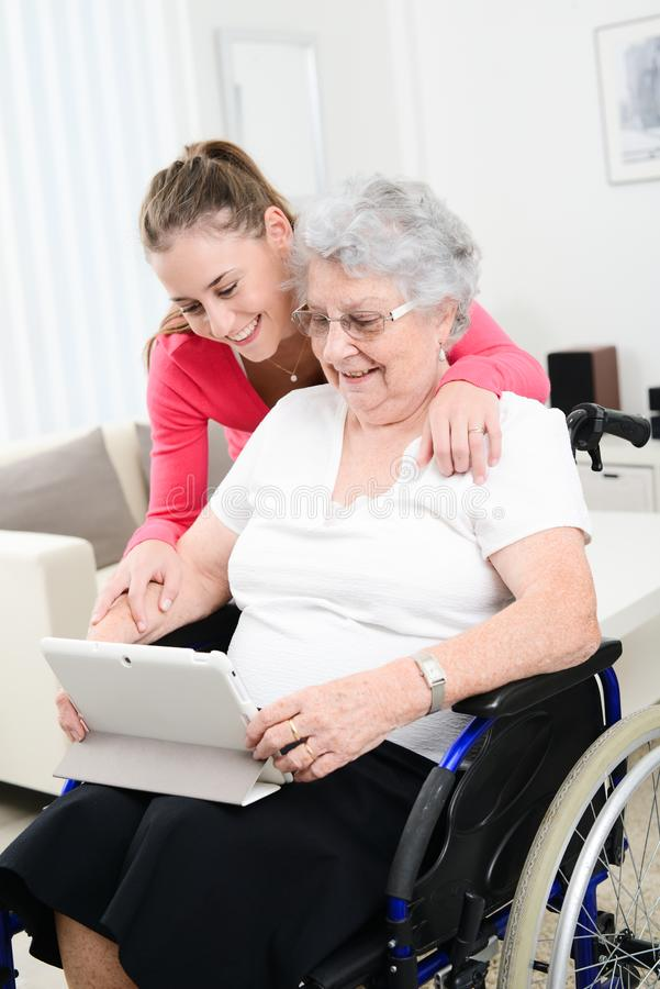 Cheerful young girl teaching internet with computer tablet and sharing time with an old senior woman on wheelchair. Cheerful young girl teaching internet with a royalty free stock photography