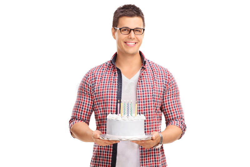 Cheerful young guy holding a birthday cake. And looking at the camera isolated on white background royalty free stock image