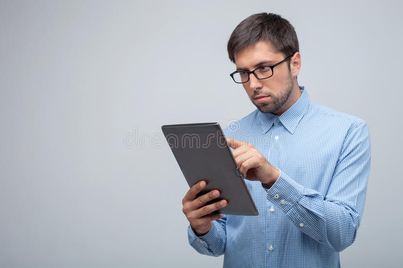 Cheerful young guy is working with internet. Attractive man is holding a laptop and touching it with seriousness. He is working on his project. Isolated on grey royalty free stock image