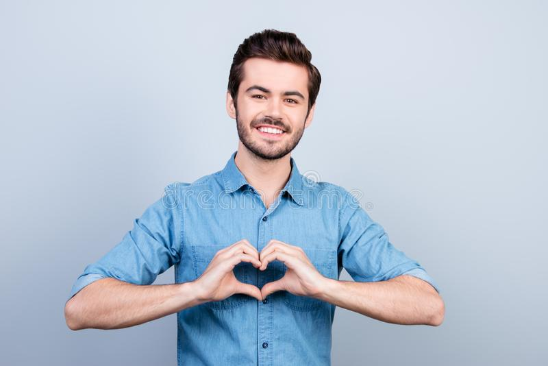 Cheerful young handsome man is gesturing a heart with fingers. H stock image