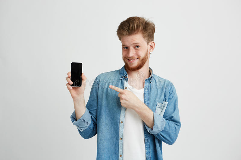 Cheerful young handsome man smiling looking at camera pointing finger at smartphone in his hand over wite background. Copy space stock images