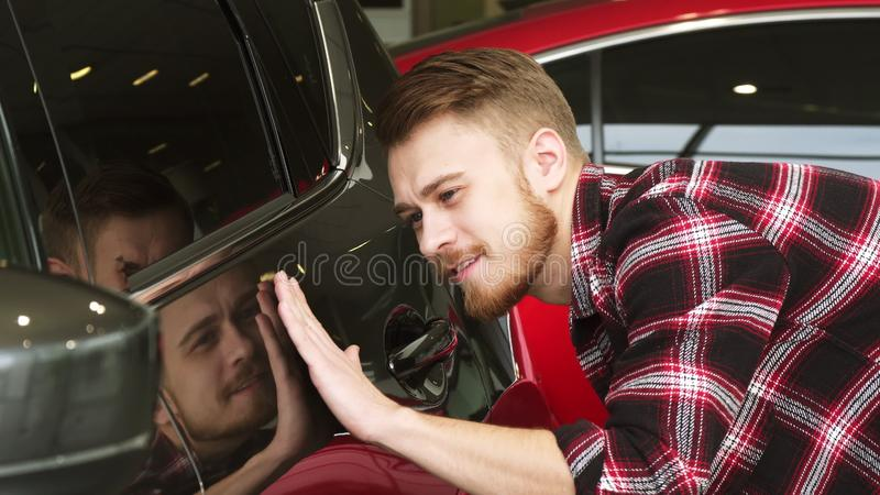 Handsome bearded male customer examining car paint on a new auto at the dealership. Cheerful young handsome man smiling touching a new auto at the dealership royalty free stock image