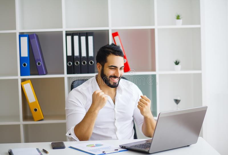Cheerful young handsome modern director working on a laptop in h. Is large bright office royalty free stock photos