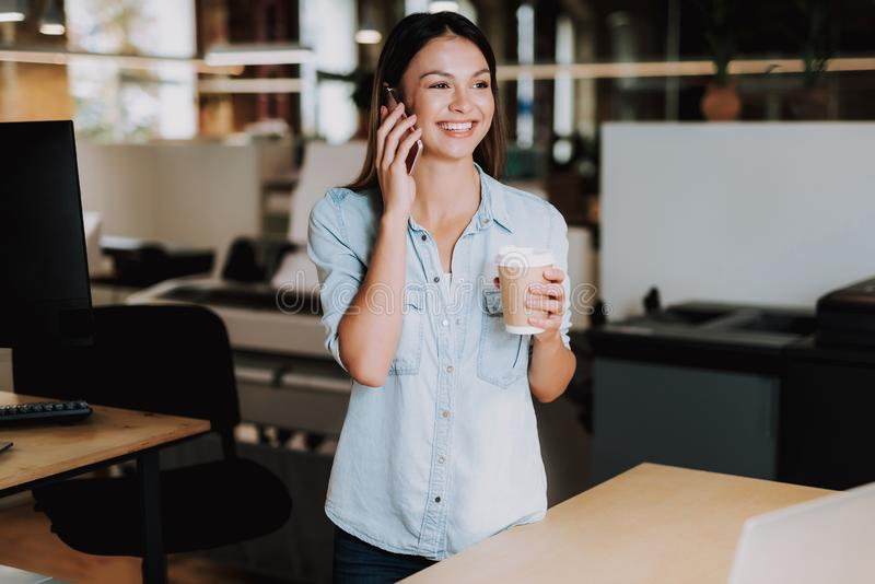 Cheerful young lady with hot drink having phone conversation at office stock images