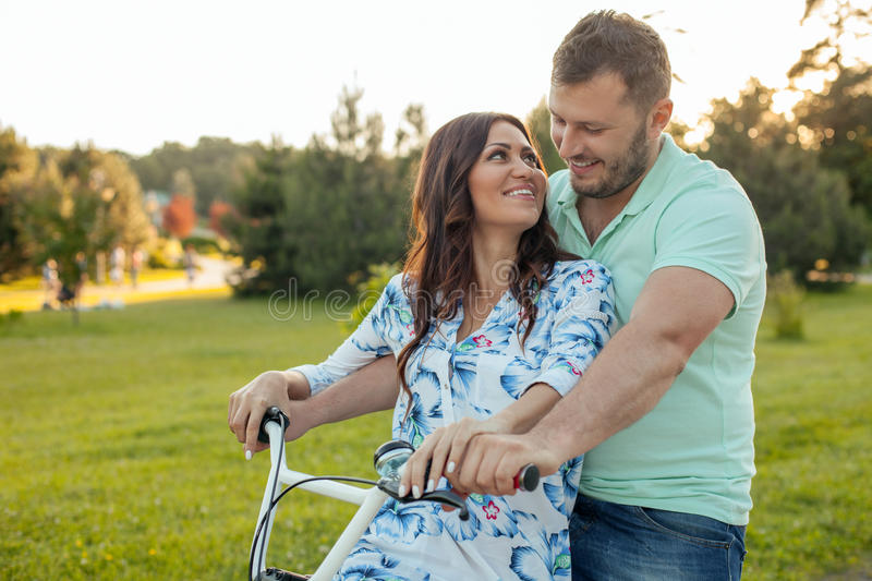 Cheerful young loving couple is cycling in park stock photos
