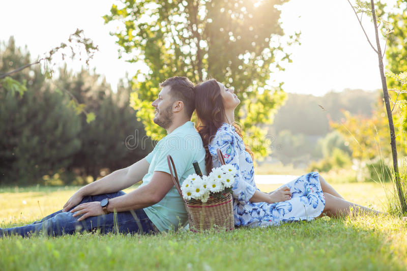 Cheerful young loving couple is relaxing in park stock photos