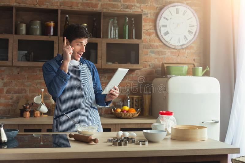 Cheerful young man baking in loft kitchen stock images