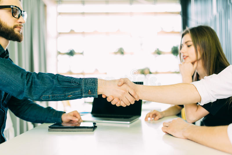 Cheerful young man bonding to his wife while shaking hand to man sitting in front of him at the desk. Good deal. Cheerful young men bonding to his wife while royalty free stock images