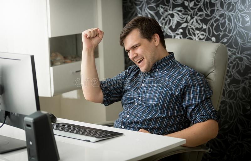 Portrait of cheerful young man celebrating success in job at office royalty free stock photo