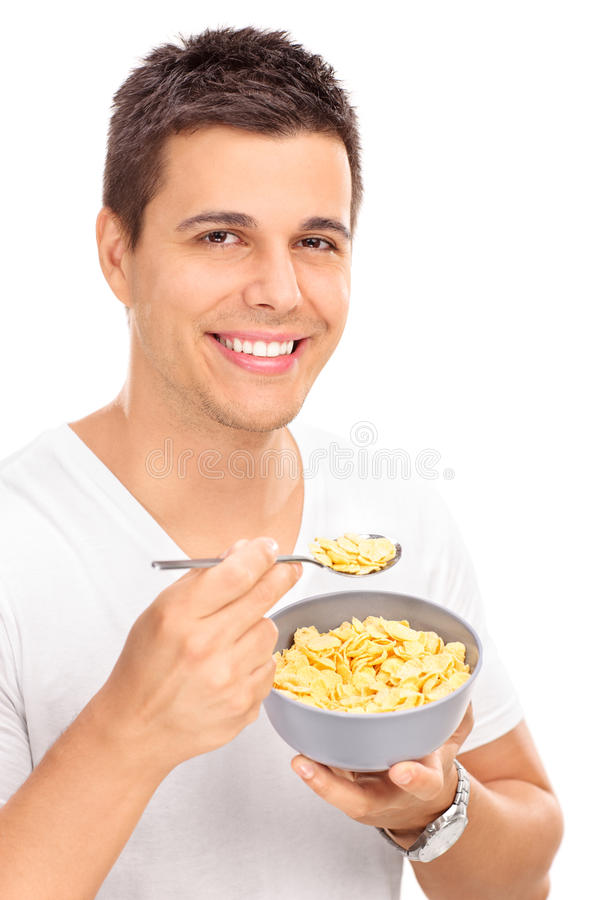 Cheerful young man eating cereal with a spoon royalty free stock photography