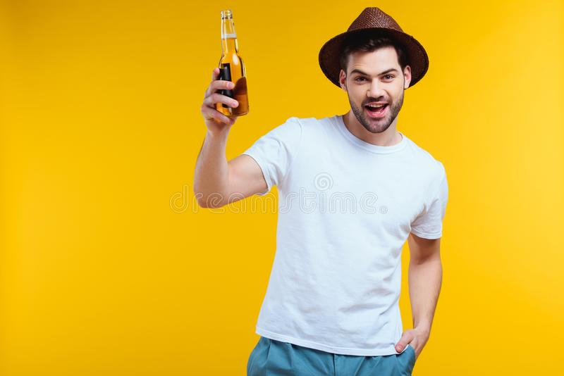 Cheerful young man in hat holding glass bottle of summer drink and smiling at camera. Isolated on yellow stock photography