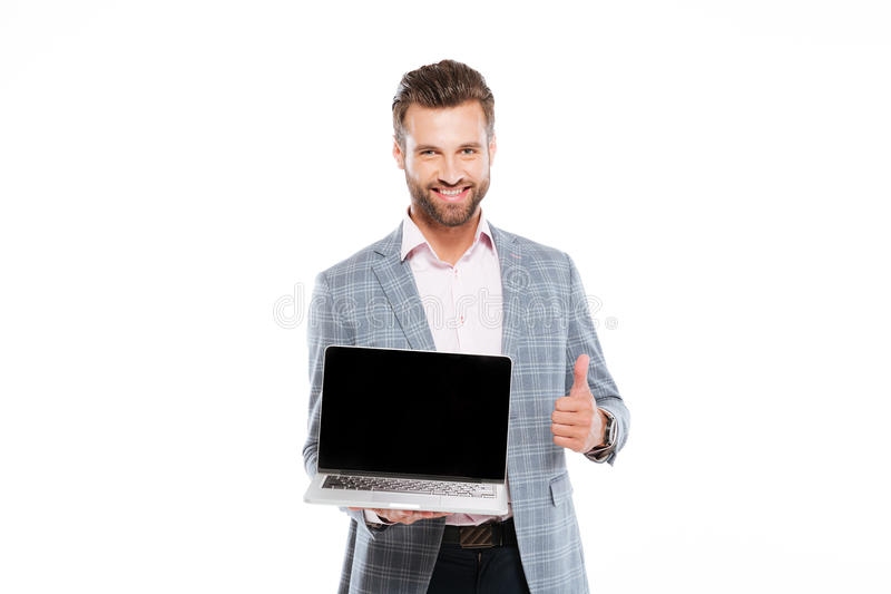 Cheerful young man holding laptop showing thumbs up. Image of cheerful young man standing isolated over white background and holding laptop computer. Looking at royalty free stock image