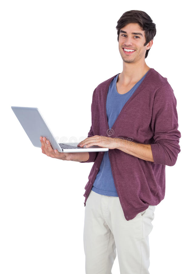 Cheerful young man holding a laptop. On a white backgound stock image