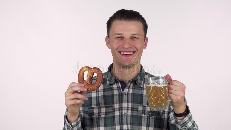 Cheerful young man holding mug of beer, smelling delicious pretzel royalty free stock images
