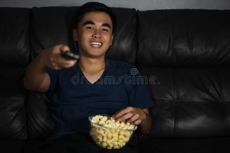 cheerful man holding remote control and watching TV while sitting on sofa at night stock images