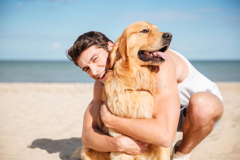 Cheerful young man hugging his dog on the beach. Cheerful young man smiling and hugging his dog on the beach royalty free stock photo