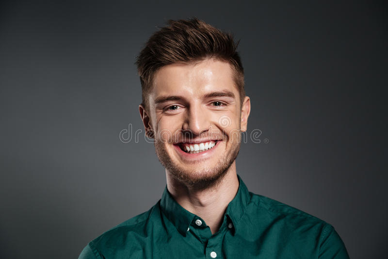 Cheerful young man posing isolated over grey background. Photo of cheerful young man posing isolated over grey background. Looking at camera royalty free stock photo