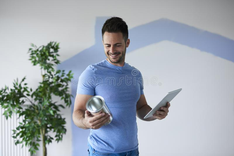 Cheerful man renovating his new apartment. Cheerful young man renovating his new apartment stock photos