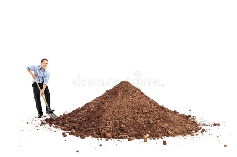 Cheerful young man shoveling a big pile of dirt. And looking at the camera isolated on white background royalty free stock photo