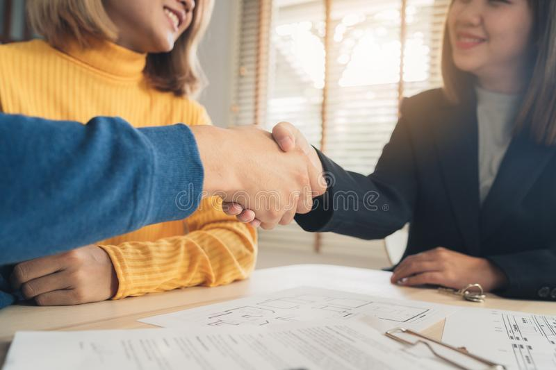 Cheerful young man signing some documents and handshaking with broker while sitting at desk. Happy young Asian couple and realtor agent. Cheerful young men royalty free stock image