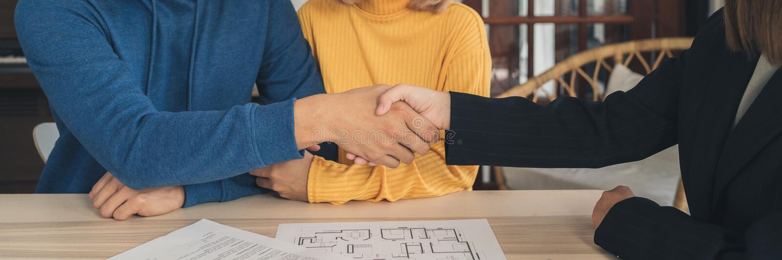 Cheerful young man signing some documents and handshaking with broker while sitting at desk. Happy young Asian couple and realtor agent. Cheerful young man royalty free stock photos