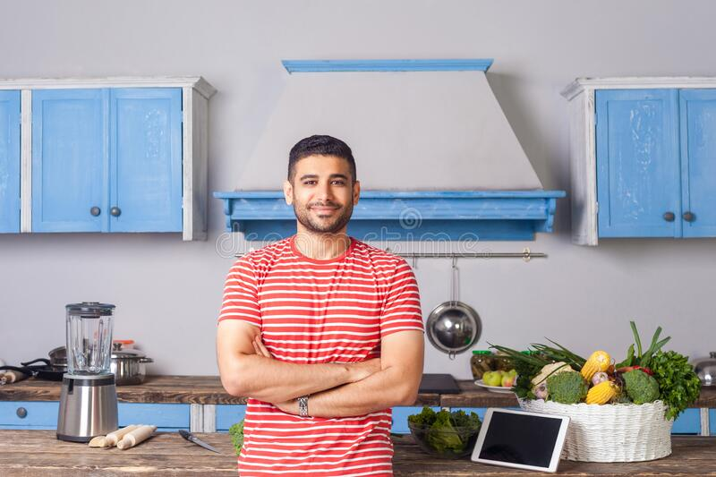 Cheerful young man standing with crossed hands in modern kitchen, looking at camera with toothy smile. Tablet pc and fresh green vegetables on table behind royalty free stock photo