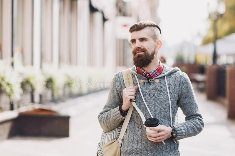 Cheerful young man wearing warm clothes walking outdoors royalty free stock photos