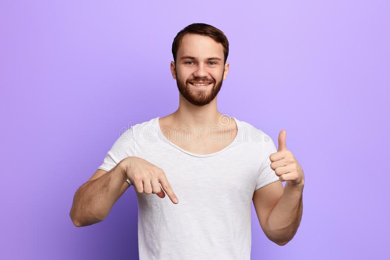 Cheerful young man in white T-shirt pointing down and showing thumb up stock image