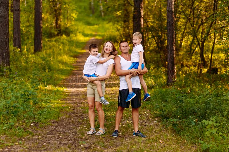 Cheerful young man and woman holding two children in the summer outdoors. family stock image