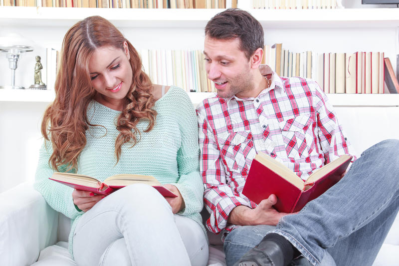 Cheerful young man and woman reading different books together while sitting clode to each other. Reading a different books together. Cheerful young men and women royalty free stock photography
