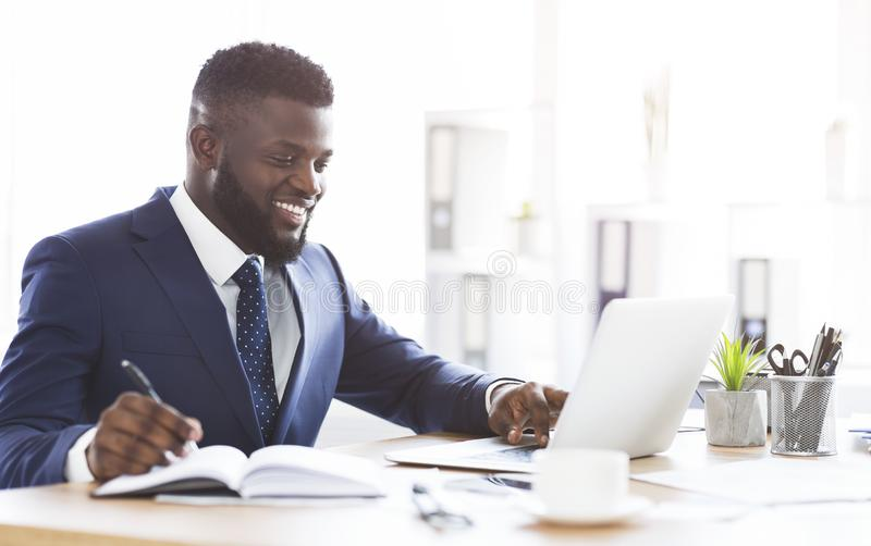 Cheerful young manager making market research online royalty free stock photo