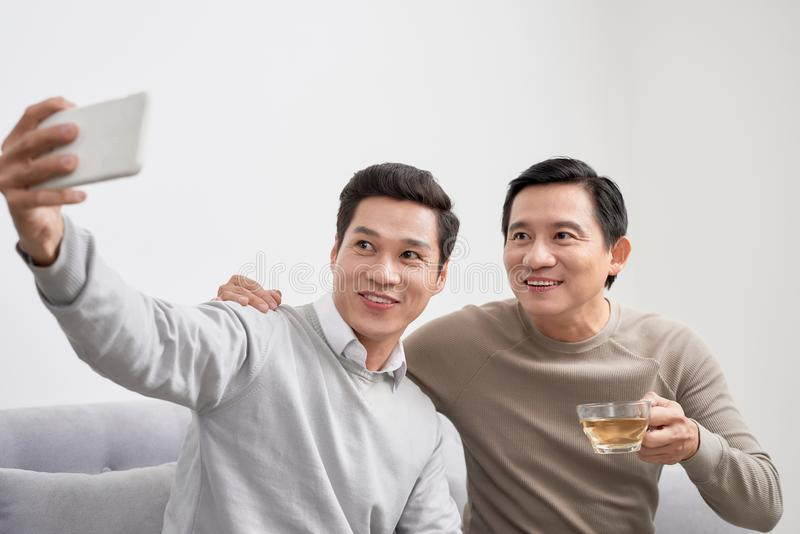 Cheerful young men dressed in casual wear smiling at camera while making selfie photo on front camera stock images