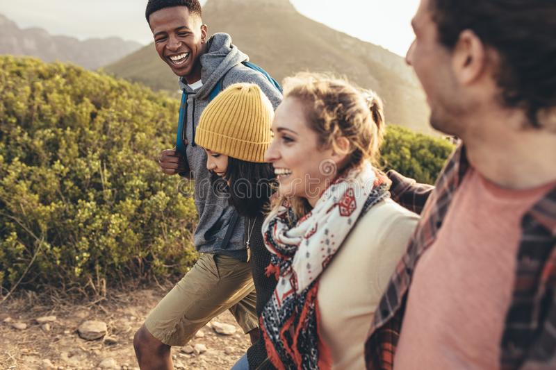 Friends having fun on their hiking trip. Cheerful young men laughing while hiking with friends. Friends having fun on their hiking trip stock photography