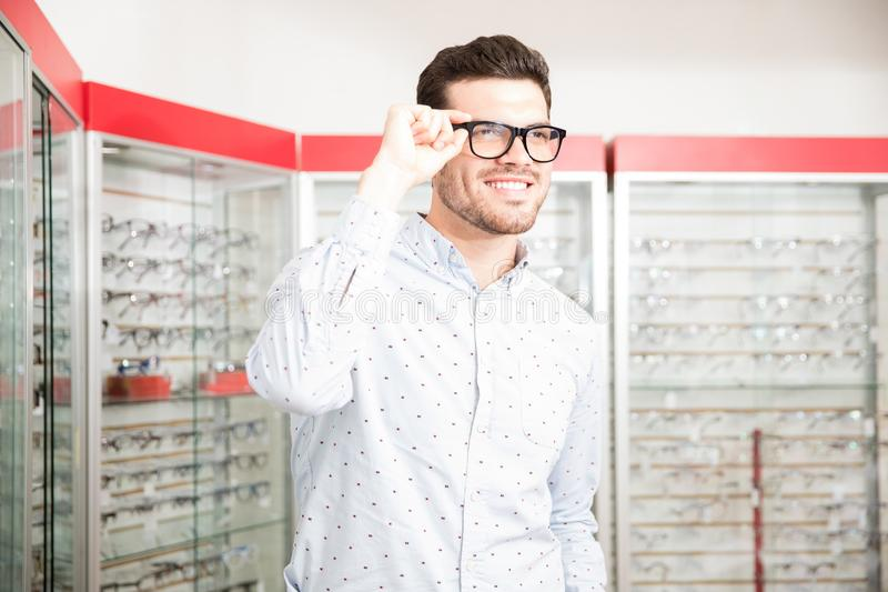 Handsome man chooses spectacle frames in the optical salon royalty free stock photo