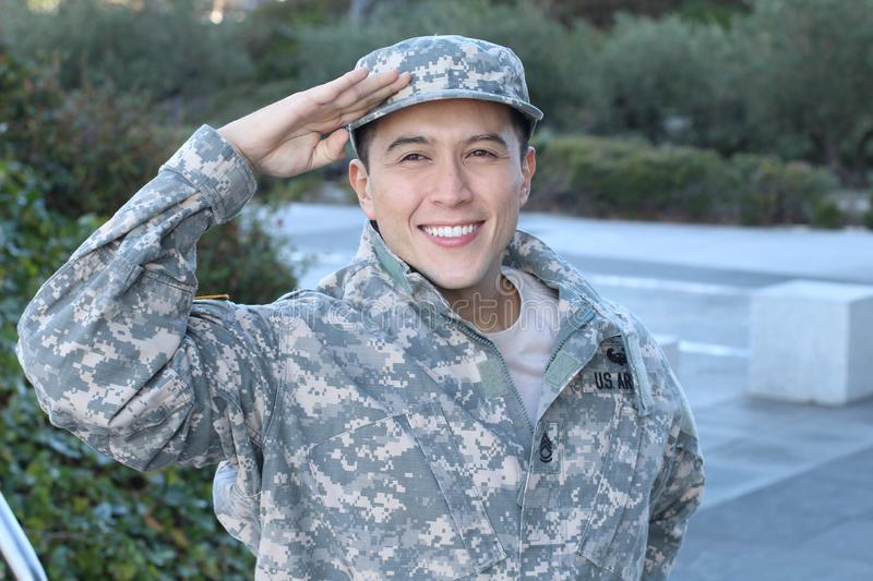 Cheerful young military soldier saluting.  stock photo
