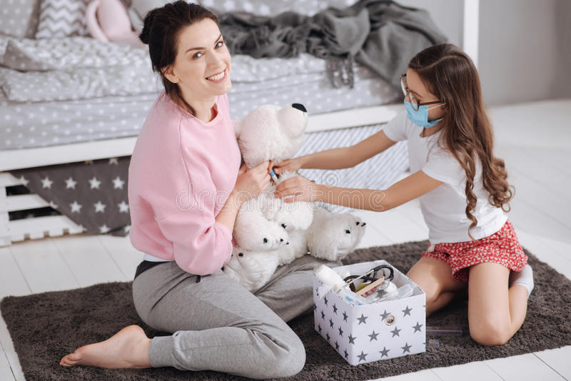 Cheerful young mother and daughter playing games at home stock photos