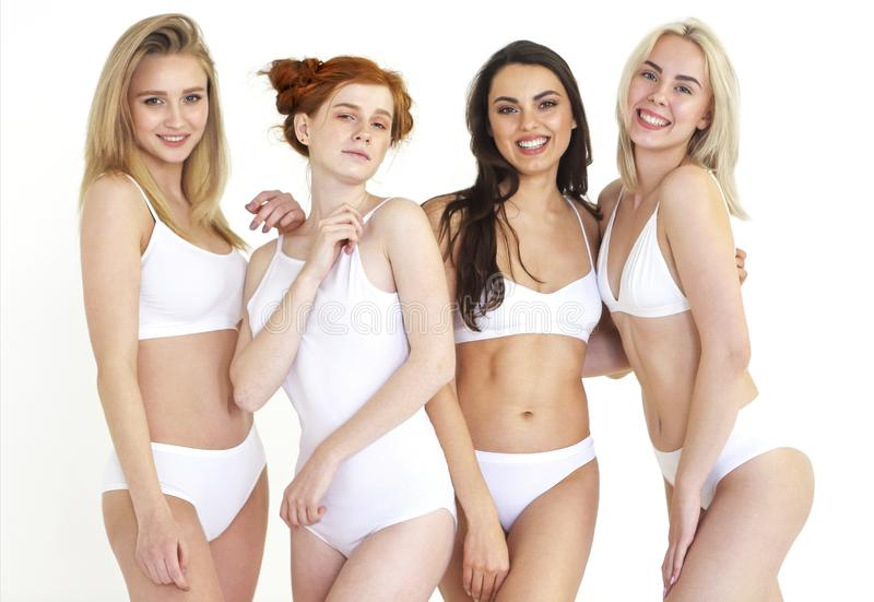 Cheerful young multiethnic women in white lingerie together stock images