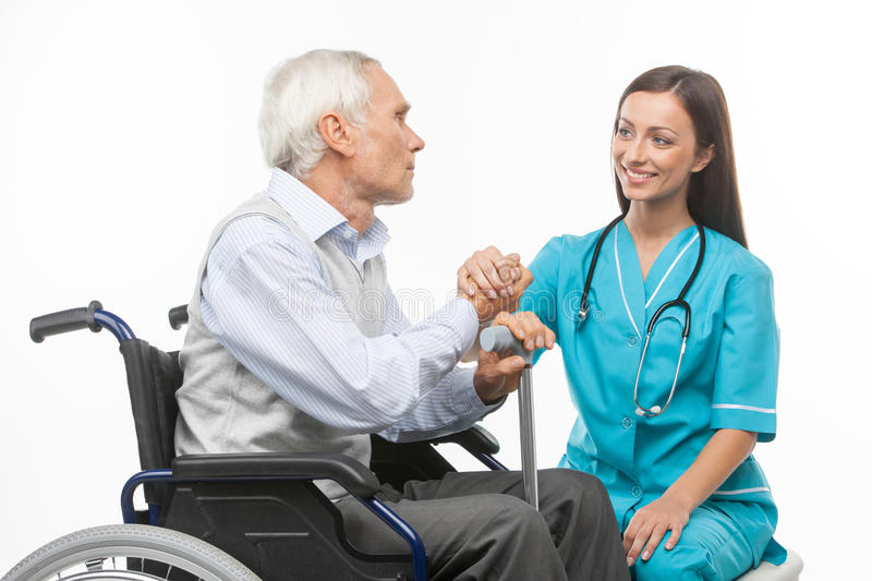 Cheerful young nurse holding senior man hand and sm stock image